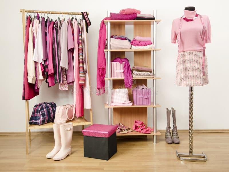Одевать шкаф с розовыми одеждами аранжировал на вешалках и полке. стоковое изображение