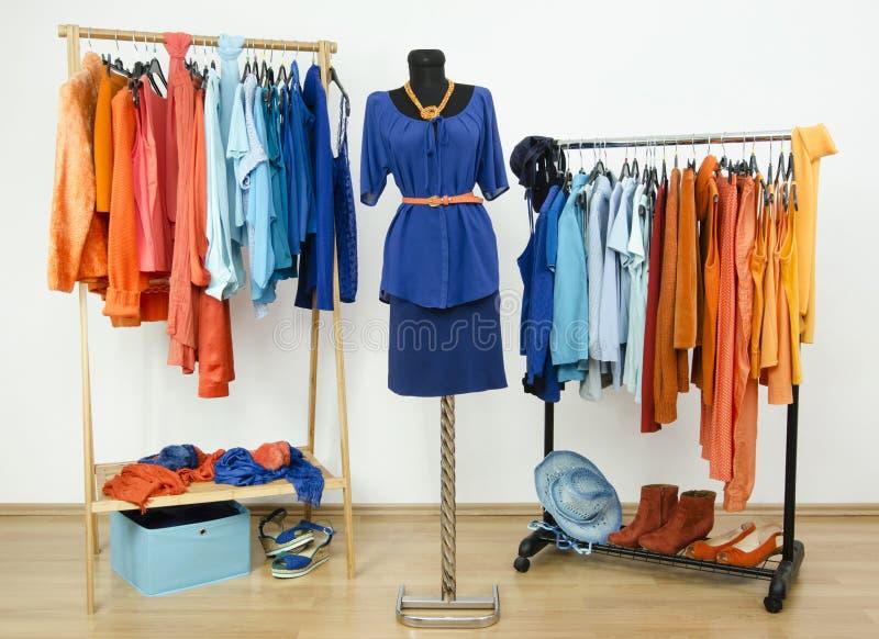 Одевающ шкаф с комплементарными цветами голубыми и оранжевыми одеждами. стоковое фото