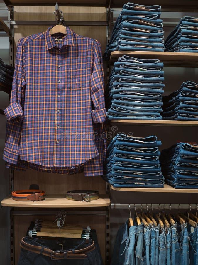 Одежда джинсовой ткани в магазине Магазин с аккуратно аранжированный с casu стоковые фотографии rf