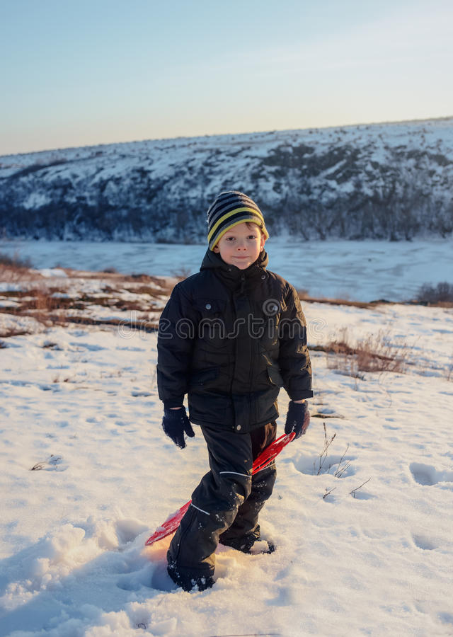 Одежда зимы мальчика портрета счастливая имея потеху в свежем белом снеге зимы в свете вечера стоковое фото rf