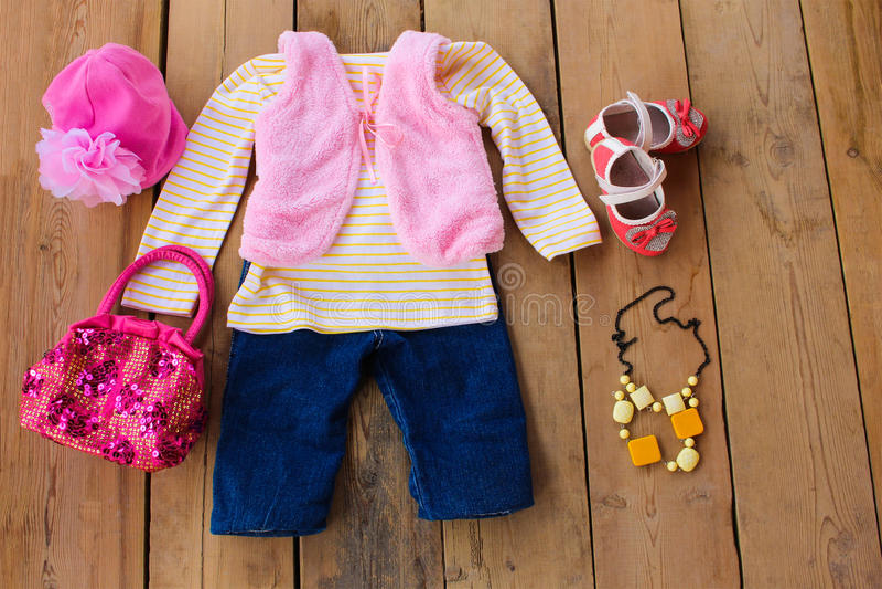 Одежда и аксессуары детей: жилет, джинсы, куртка, ботинки, шляпа и сумка стоковые фото