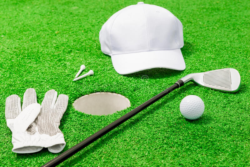 Одежда и инструменты для игры гольфа около отверстия стоковое изображение