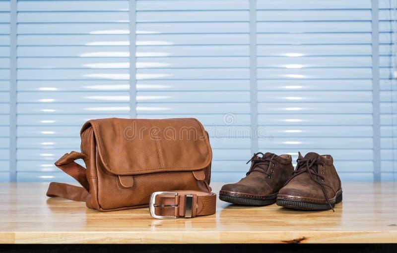 Одежда моды кожи ` s людей, ботинки, сумка и пояс на переклейке t стоковое изображение rf