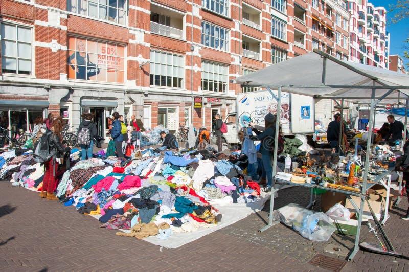 Одежда продажи подержанная на ежедневном блошинном на Waterlooplein (квадрате Ватерлоо), купцах показывает их bric-a-brac для про стоковые изображения