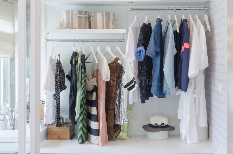 Одежды вися в шкафе с шляпой стоковое фото