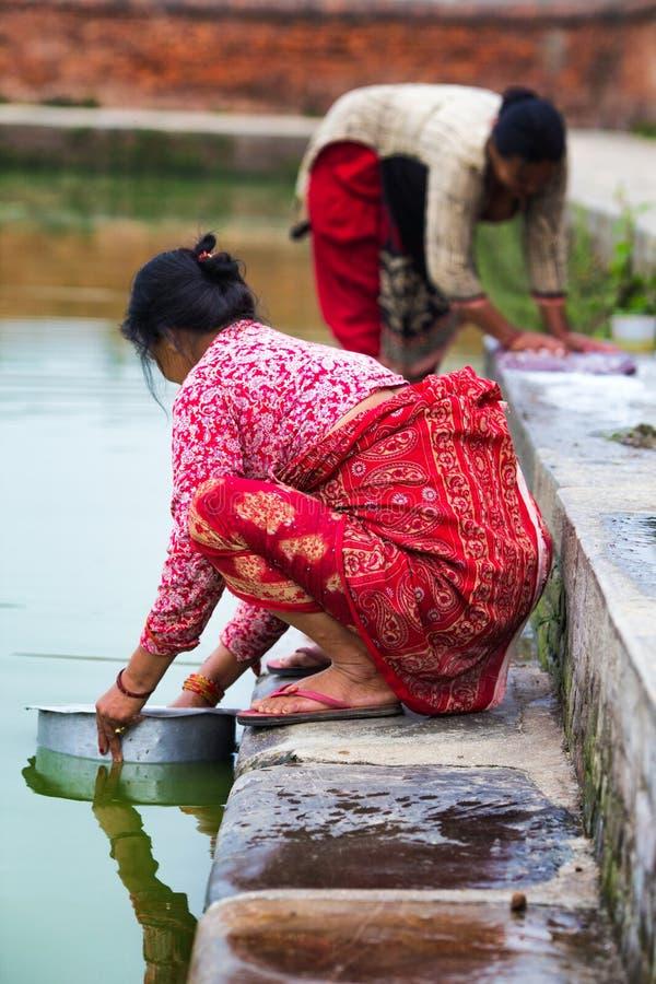 Одежды женщины моя в озере стоковое фото
