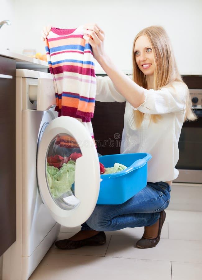 Одежды женщины looling приближают к стиральной машине стоковое изображение rf