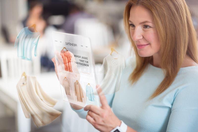 Одежды жизнерадостной приятной женщины покупая онлайн стоковые изображения