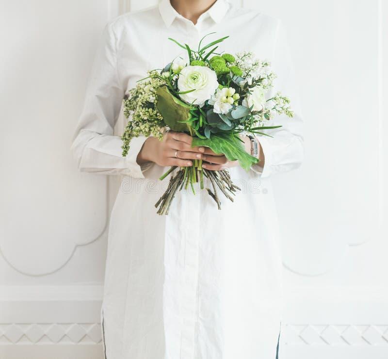 Одежды молодой женщины нося белые держа букет, белую предпосылку стены стоковые изображения