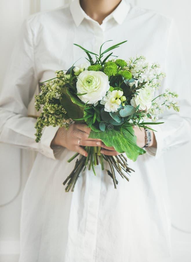 Одежды молодой женщины нося белые держа букет Концепция цветочного магазина стоковая фотография rf