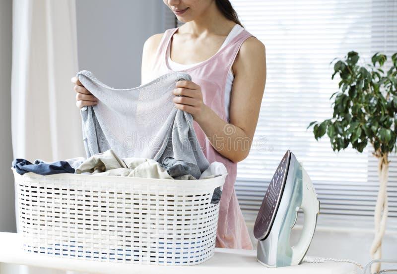 Одежды молодой женщины утюжа на утюжа доске стоковая фотография rf