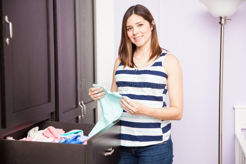 Одежды младенца беременной женщины складывая стоковая фотография rf