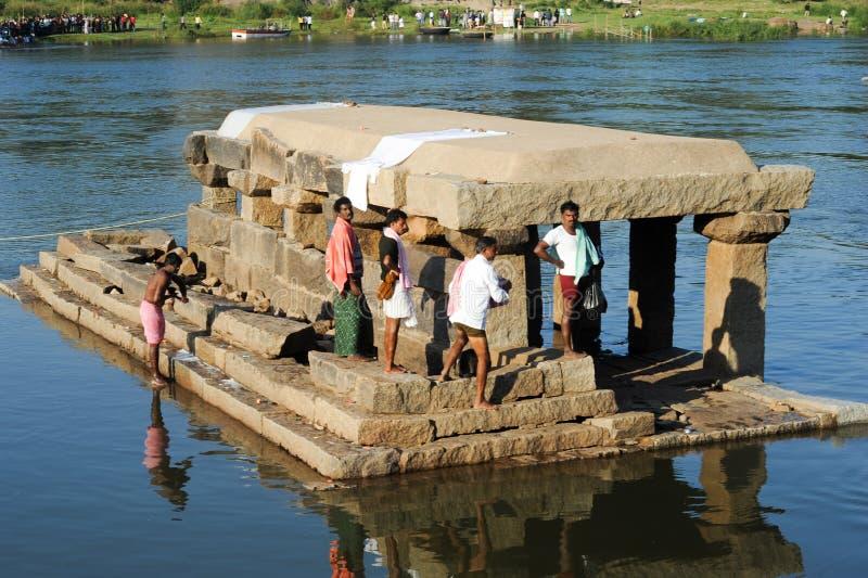 Одежды сами людей моя и в реке на Hampi стоковое фото