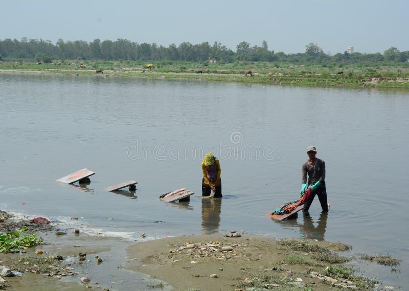 Одежды людей моя на реке стоковое фото