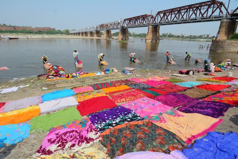 Одежды людей моя на реке стоковая фотография