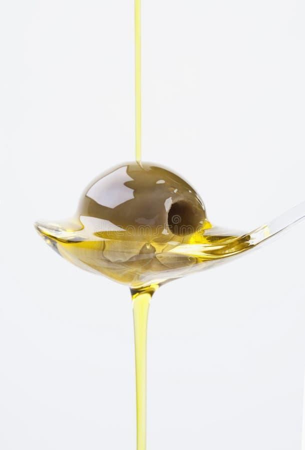 Оливка на ложке при оливковое масло лить сверх стоковые изображения