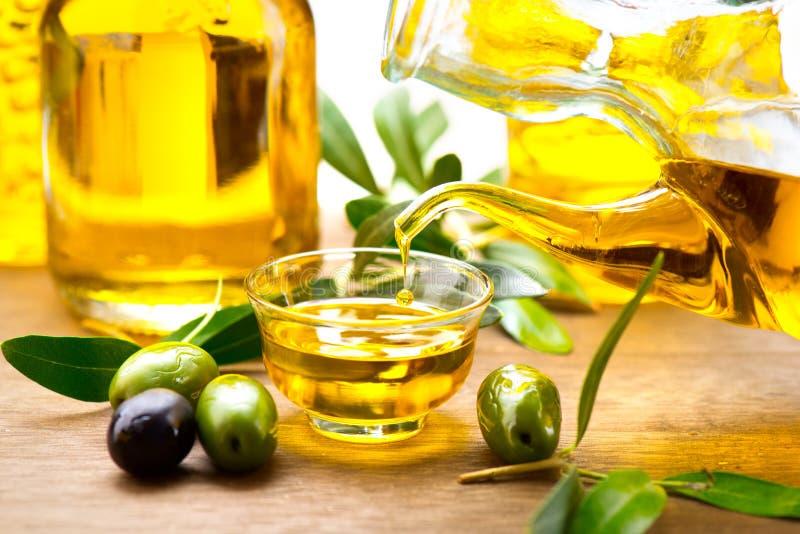 Оливковое масло девственницы лить в шаре стоковое фото