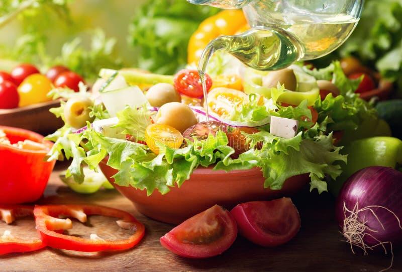 Оливковое масло лить в шар vegetable салата стоковое фото
