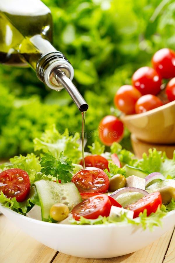 Оливковое масло лить над салатом стоковое фото rf