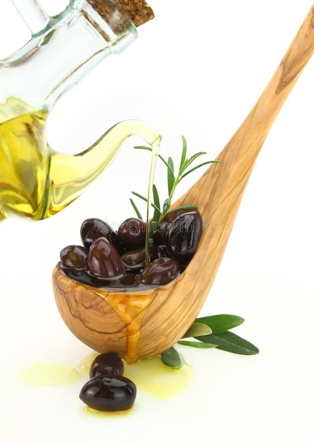 Оливковое масло полило в деревянную ложку вполне оливок стоковые фотографии rf