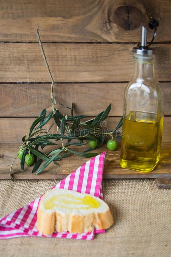 Оливковое масло с оливками на деревянной доске стоковое фото