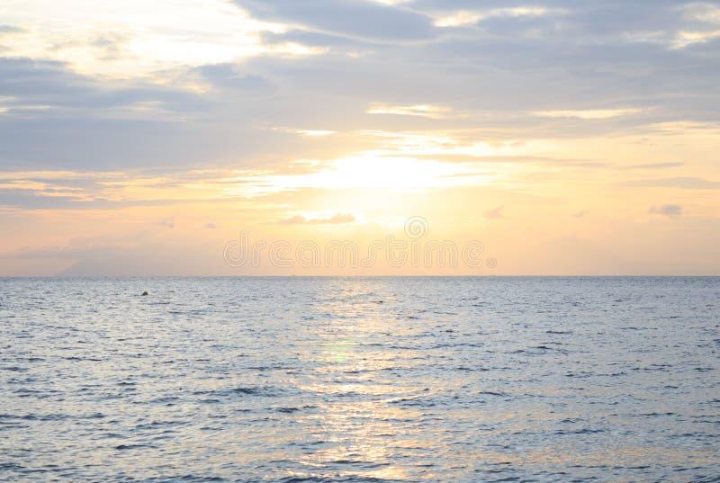 Одиночества утра заход солнца желтого цвета ясно теплый и выплеск моря развевают поверхность воды, остров Таиланд Lipe стоковые изображения rf