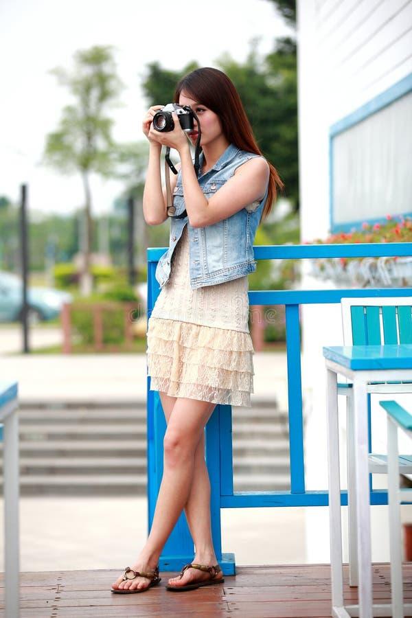 Одиночная азиатская молодая женщина с камерой стоковое изображение rf