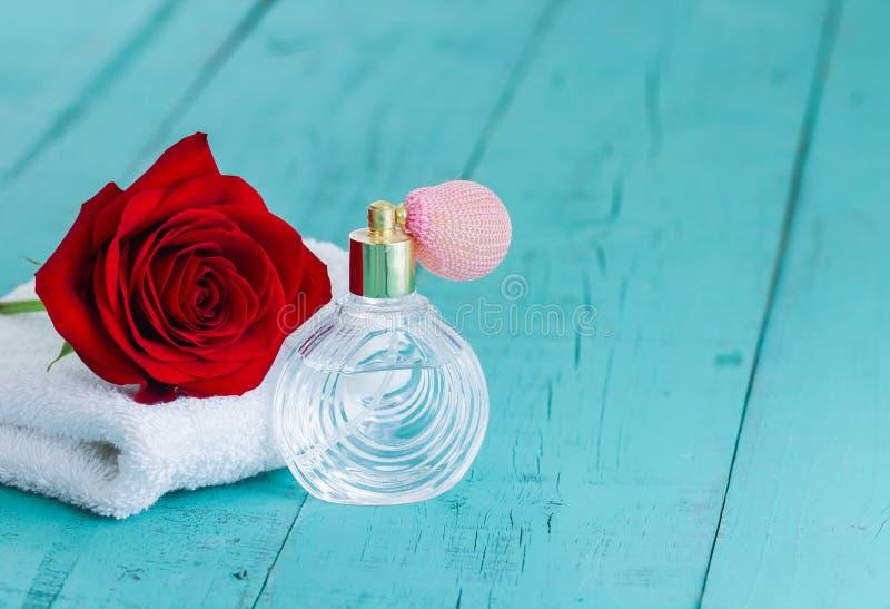 Одиночные красная роза и флакон духов на предпосылке teal голубой деревянной стоковое изображение