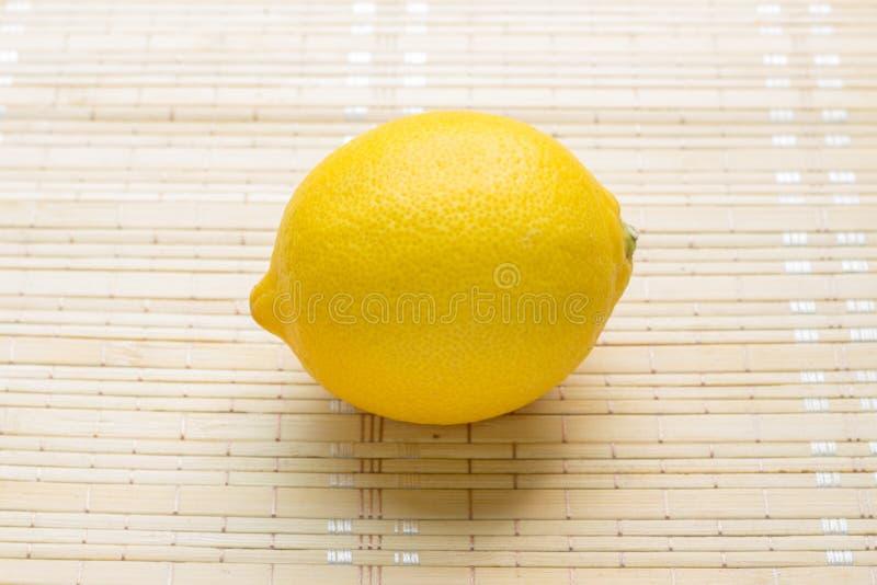 Одиночный лимон на бамбуковой предпосылке циновки стоковое изображение rf