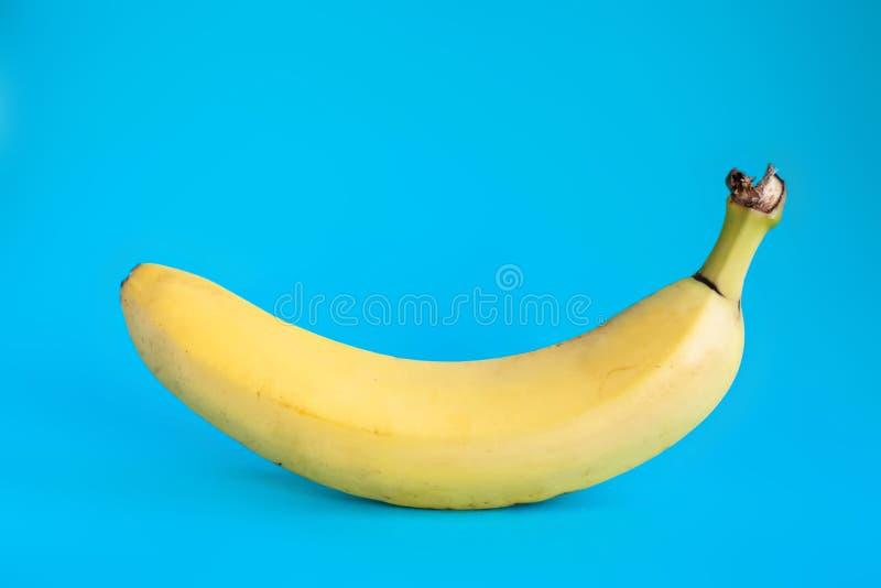 Один банан на сини стоковое фото