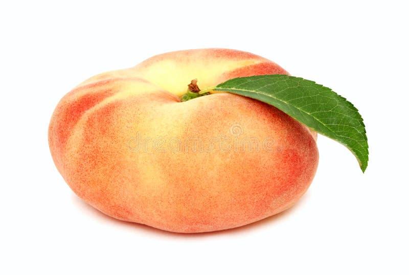 Один весь плоский персик при зеленые (изолированные) лист стоковая фотография