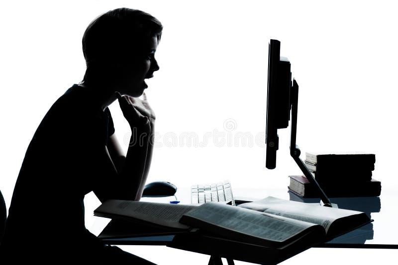 Один молодой силуэт девушки мальчика подростка изучая с компьютером c стоковое фото rf