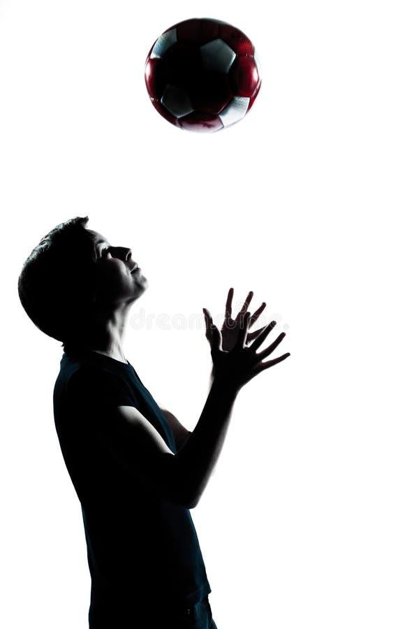 Один молодой силуэт девушки мальчика подростка меча футбол футбола стоковое фото