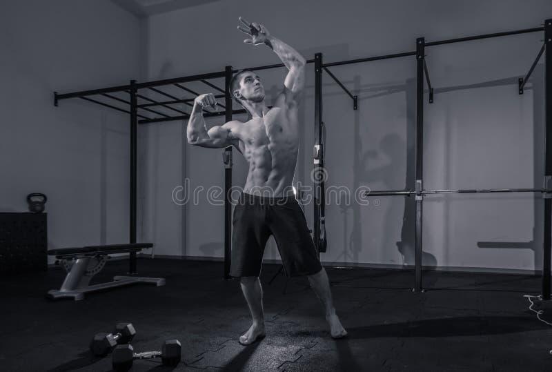Один молодой человек, без рубашки культуриста мышечный, темный спортзал внутри помещения стоковые фото