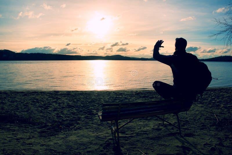 Один молодой человек в силуэте сидя в Солнце на пляже Туристские остатки взятия на деревянной скамье на озере осени стоковая фотография rf