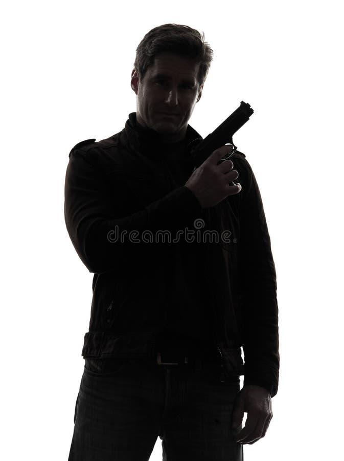 Полицейский убийцы человека держа силуэт портрета пушки стоковое изображение