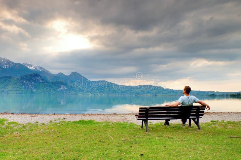 Один человек сидит на стенде около лазурного озера горы человек ослабляет стоковое фото rf