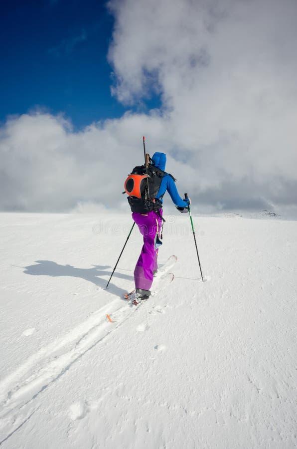 Один лыжник идя через нетронутый снег стоковые фото
