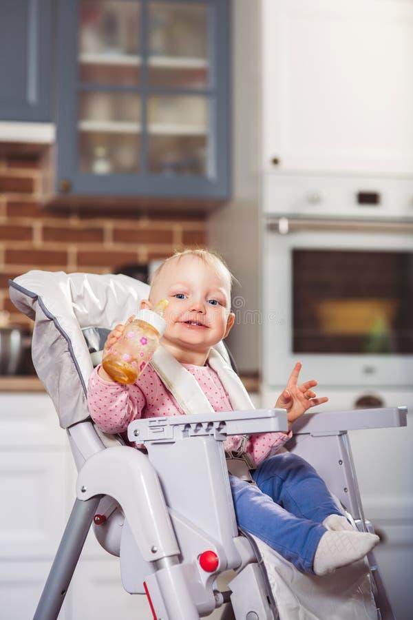 Одна девушка малыша года сидит на стуле младенца высоком с подавая бутылкой в ее руке стоковое фото