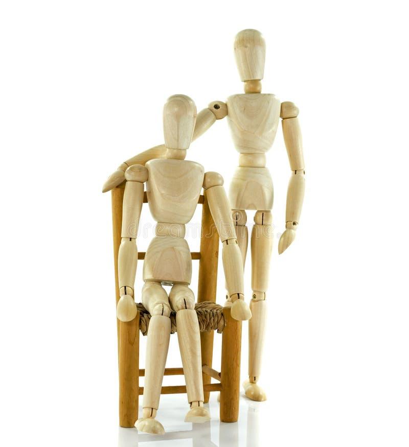 Давать медицинское соревнование к деревянной марионетке сидя на стуле стоковое фото