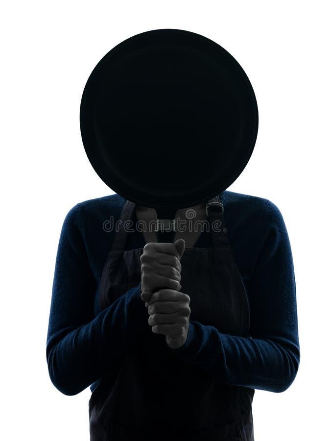 Женщина варя прятать за силуэтом сковороды стоковое фото rf