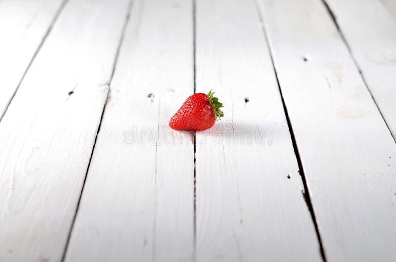 Одна клубника на белом деревянном столе стоковое изображение rf