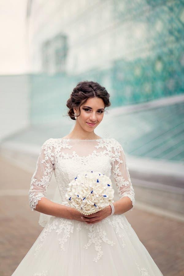 Одна милая невеста на предпосылке стеклянной городской архитектуры стоковое изображение