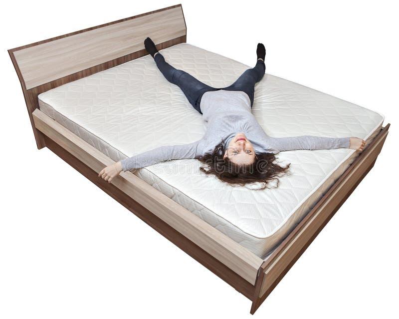 Одна молодая кавказская девушка отдыхает на тюфяке кровати innerspring стоковое фото