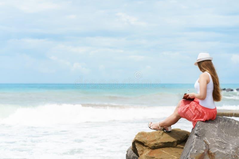 Одна довольно европейская женщина sittin на камне близко к берегу тропического моря и писать некоторые идею, письмо или работу ми стоковые изображения