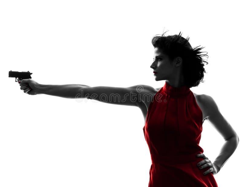 Сексуальная женщина держа силуэт пушки стоковая фотография rf