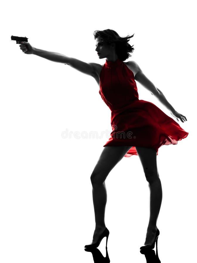 Сексуальная женщина держа силуэт пушки стоковое изображение rf