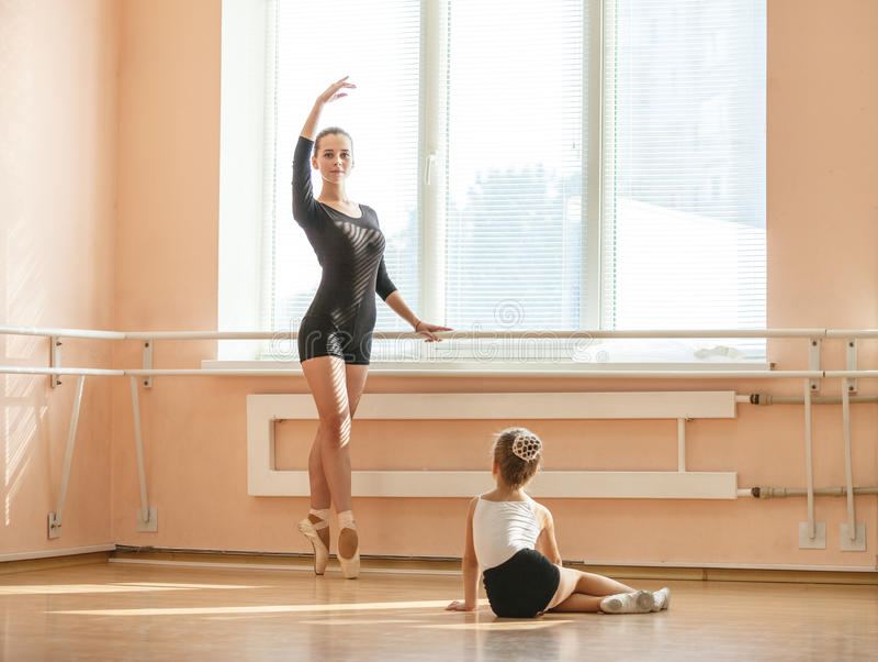 Одноклассник beginner девушки наблюдая стоя pointe en стоковые фото