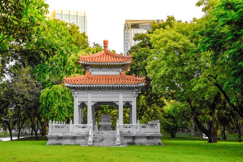 Павильон китайского стиля в парке для широкой публики, который нужно сидеть и ослабить на общественном парке Lumpini, Бангкоке, Т стоковая фотография