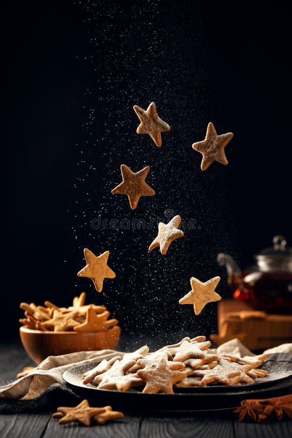 Падающие звезды сформировали печенья с напудренным сахаром Вертикальный состав на темноте стоковые фото